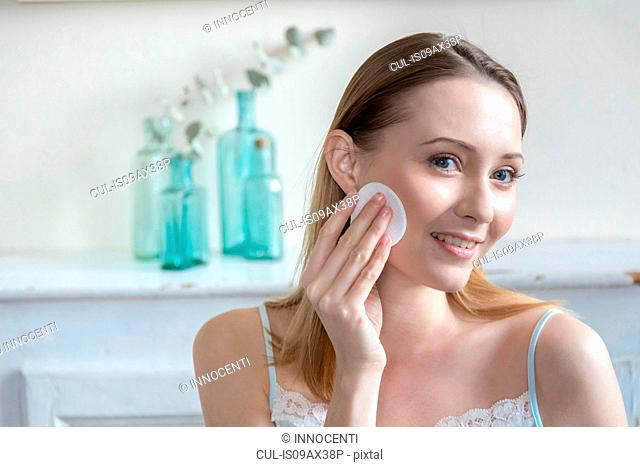 Woman moisturising face with cotton wool pad