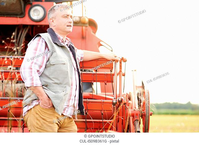 Farmer leaning against combine harvester looking away