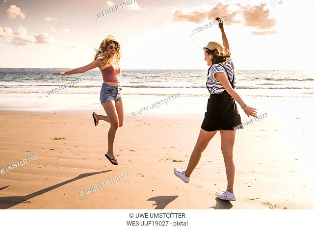 Two girlfriends having fun, running and jumping on the beach