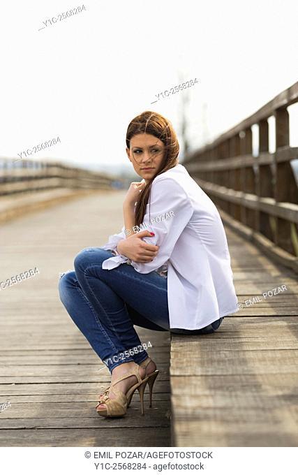 Teenager girl is cold sitting on bridge waiting looking back