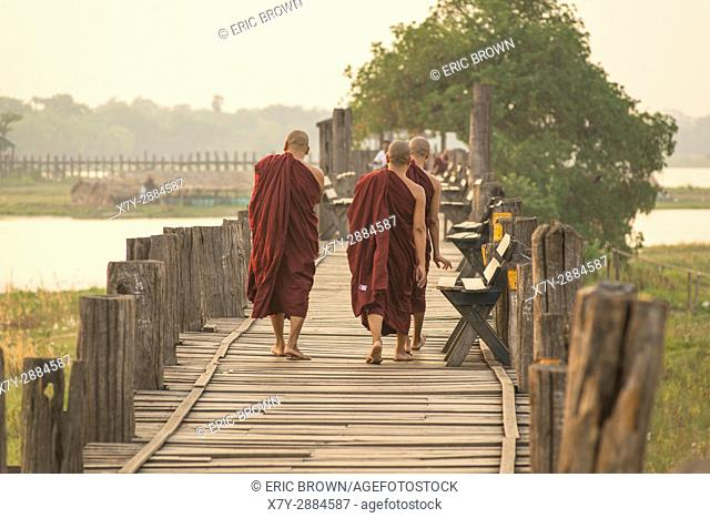 Monks waking at sunrise over U Bein Teak Bridge, Amarapura, Myanmar