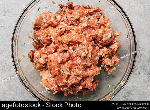 Mixed meatball ingredients in a glass bowl