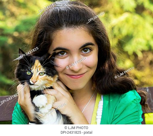 Portrait of a young girl holding a cat outdoors; Sherwood Park, Alberta, Canada