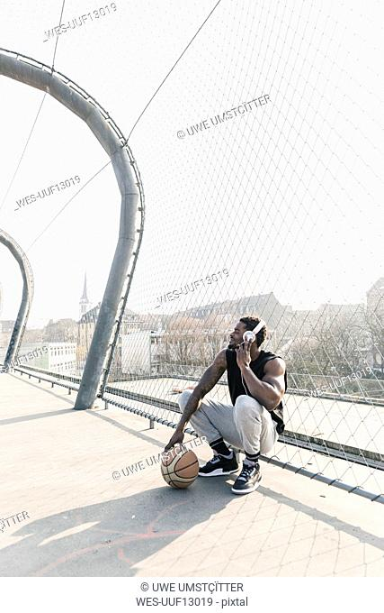 Basketball player on court crouching at fence listening to music