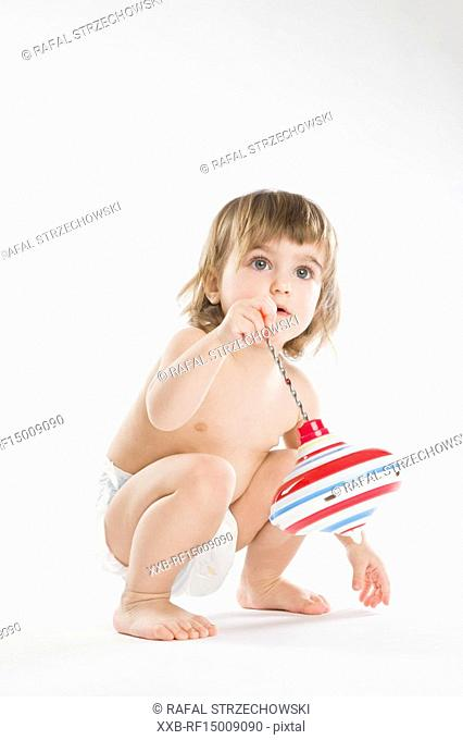 toddler girl playing with spinning top