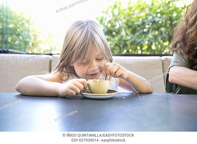 four years old blonde child sitting at the table, playing with coffee cup and spoon, next to woman in restaurant