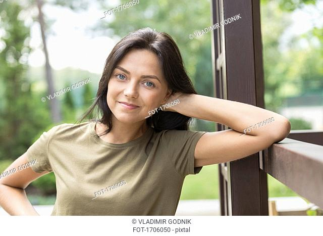 Portrait of smiling woman leaning on railing at yard