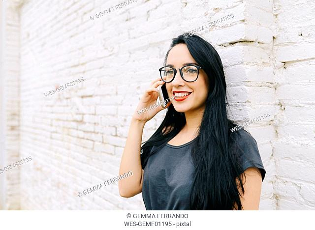 Smiling young woman on cell phone in front of brick wall