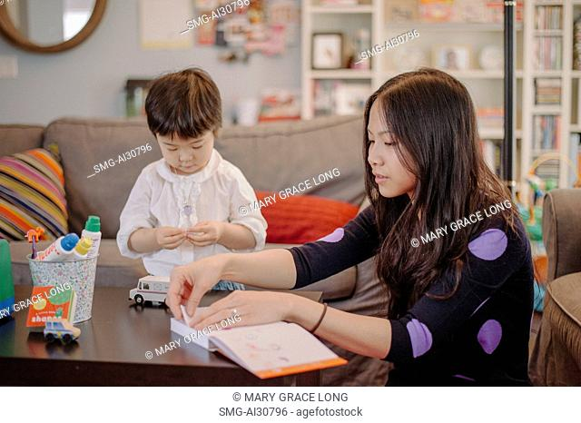 USA, Mother and daughter (2-3) sitting together in living room