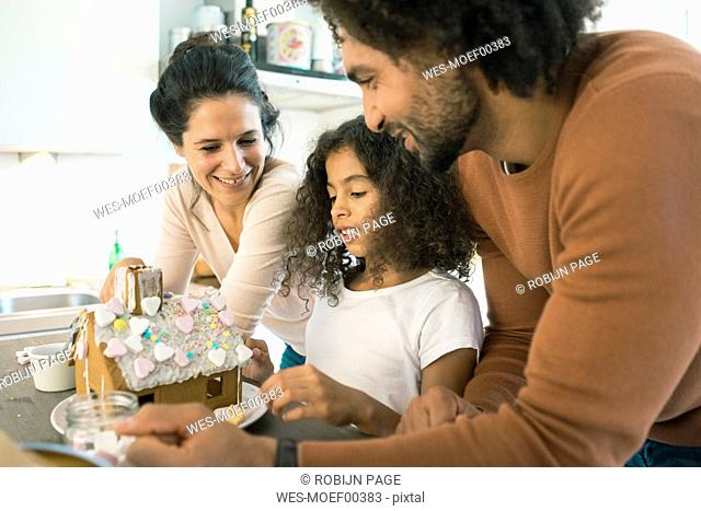 Family pasting gingerbread house in kitchen for Christmas with sweets