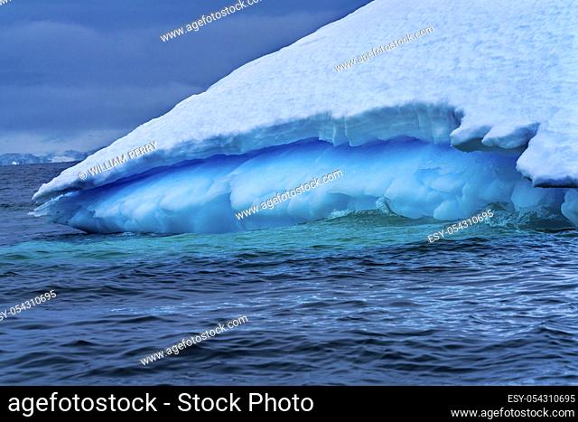Floating Blue Iceberg Floating Sea Water Charlotte Bay Antarctic Peninsula Antarctica. Glacier ice blue because air squeezed out of snow