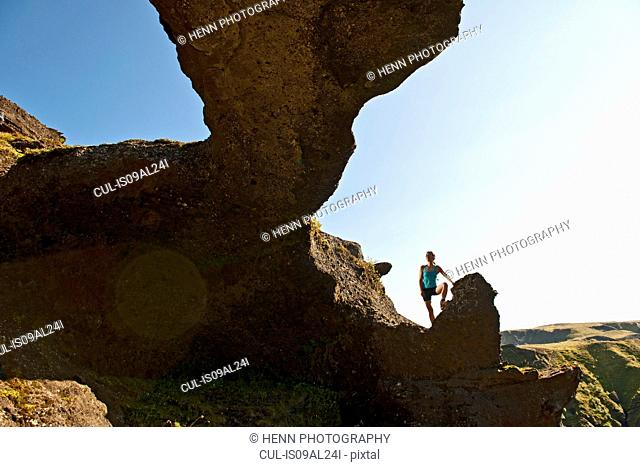 Woman standing in arch on way to Fimmvordurhals Pass above Thorsmork Valley, Thorsmork, South Iceland, Iceland