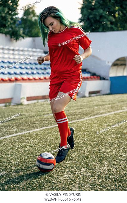 Young woman playing football on football ground dribbling with the ball