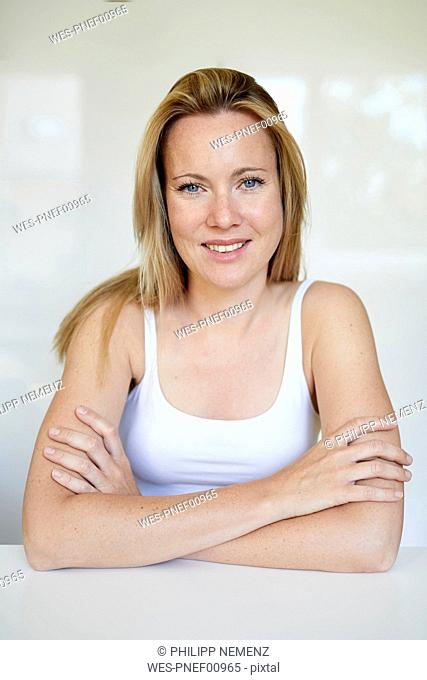 Portrait of a beautiful blond woman, with arms crossed
