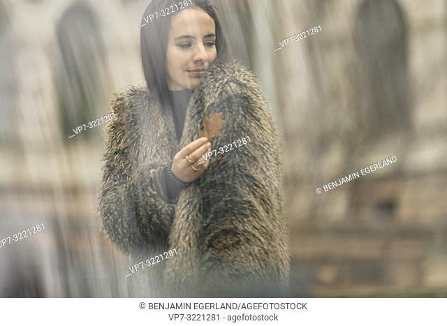woman holding autumn leave and wearing fashionable coat, in Munich, Germany