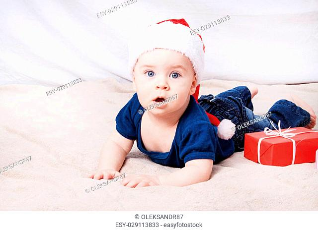 Beautiful little baby celebrates Christmas. New Year's holidays. Baby in Santa hat