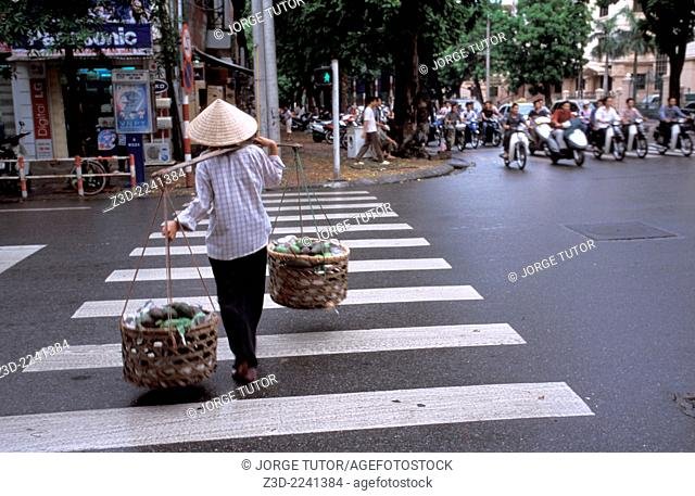 vendor walking the streets of Hanoi with her Non la palm-leaf conical hat