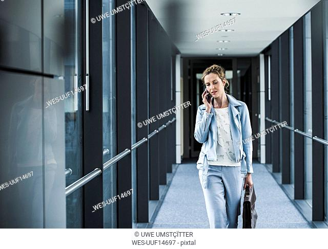 Businesswoman on cell phone walking in office passageway