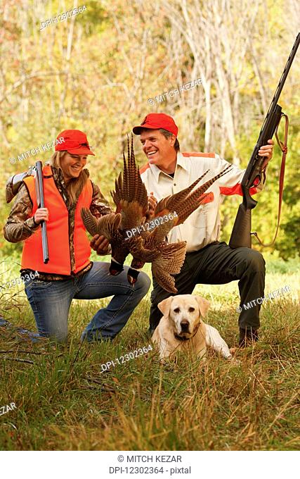 Father And Daughter Pheasant Hunters With Lab