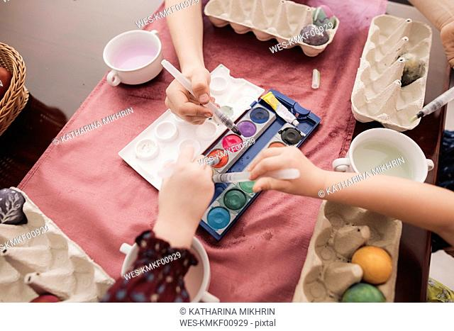 Children painting Easter eggs on table at home