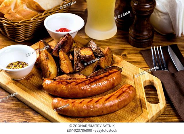 Grilled sausages with roast potato with spices