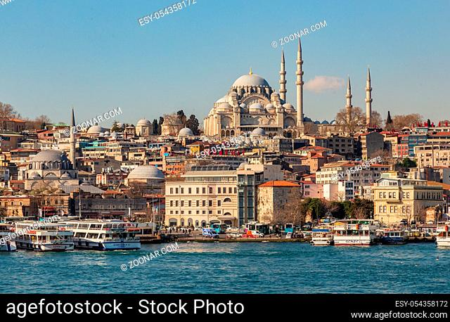 Istanbul, Turkey, 22 March 2019: View to Eminonu pier and Suleymaniye mosque across Bay of Golden Horn on sunny morning. Touristic sightseeing ships in Golden...