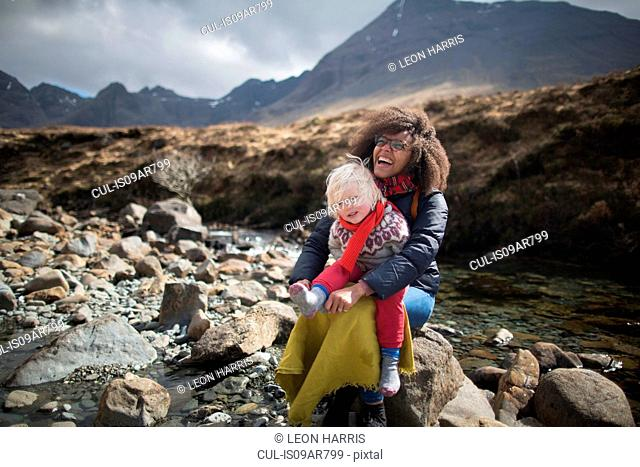 Mother and son sitting on rocks, Fairy Pools, Isle of Skye, Hebrides, Scotland
