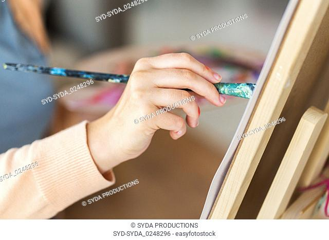 hand of artist with brush painting at art studio