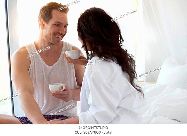 Happy young couple having coffee on bed