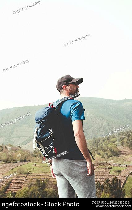 Man with cap and backpack in the mountain