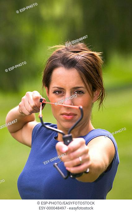 Young women aiming a slingshot