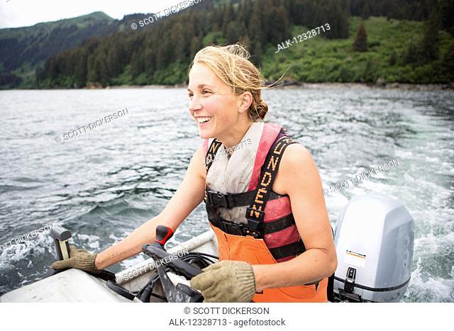 Female set-netter driving her set-net skiff near Seldovia, South-central Alaska; Alaska, United States of America