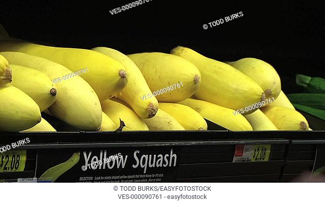 Woman selecting yellow squash in grocery