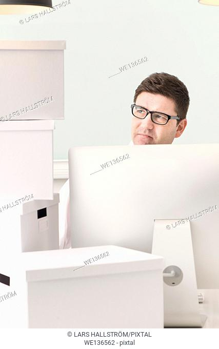 Businessman working with computer at desk. He is surrounded by white boxes used for moving. Conceptual image of business relocation, startup or change