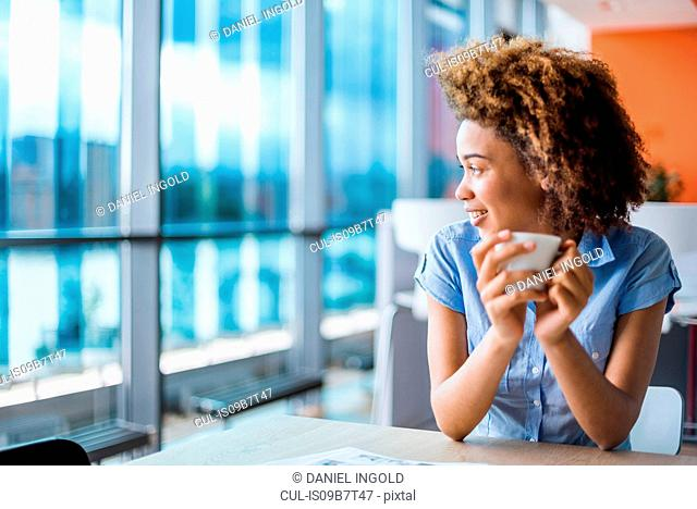 Young woman holding coffee at table gazing through window
