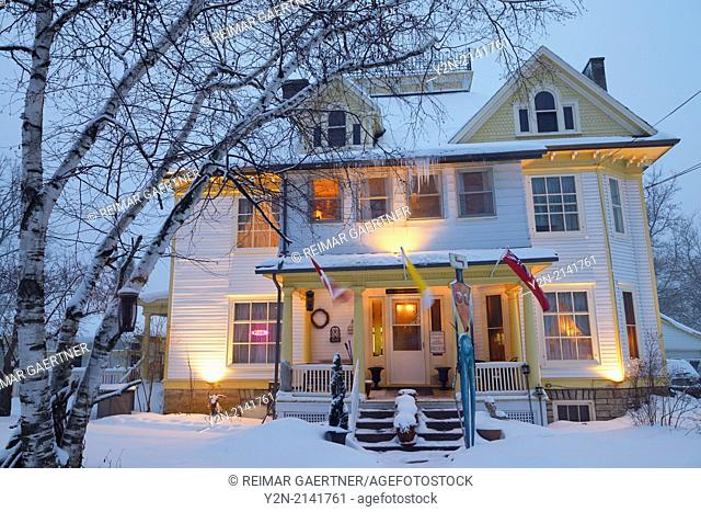 Snow covered heritage home at dusk in the small town of Marmora Ontario