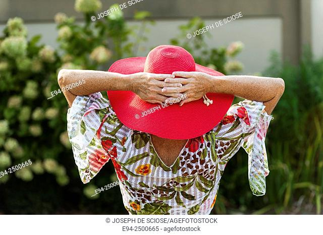 Back view of a 56 year old blond woman wearing a red hat and a casual summer top