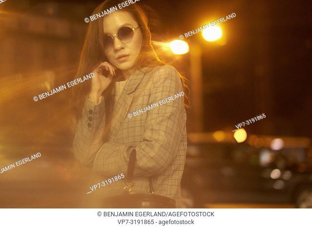 Fashionable woman on the street by night. Munich, Bavaria, Germany