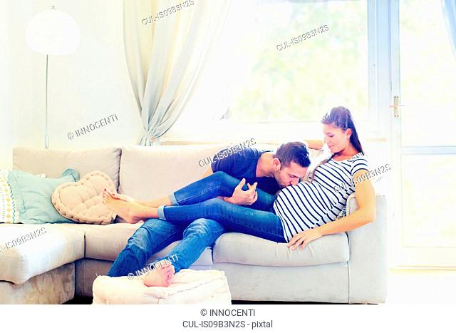 Man on sofa kissing pregnant woman's stomach