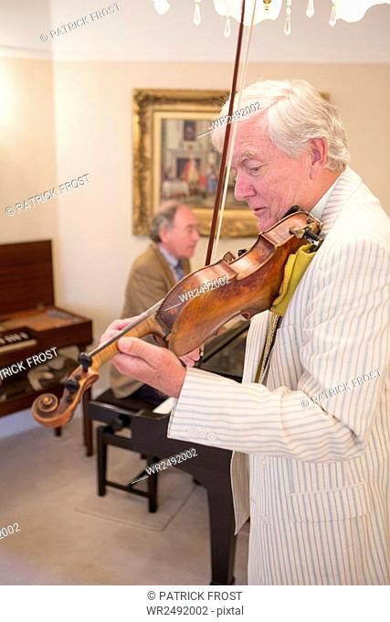 Two senior men playing music together