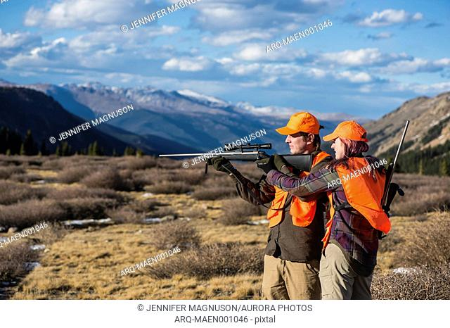 Side view shot of female hunter teaching male hunter about operating rifle