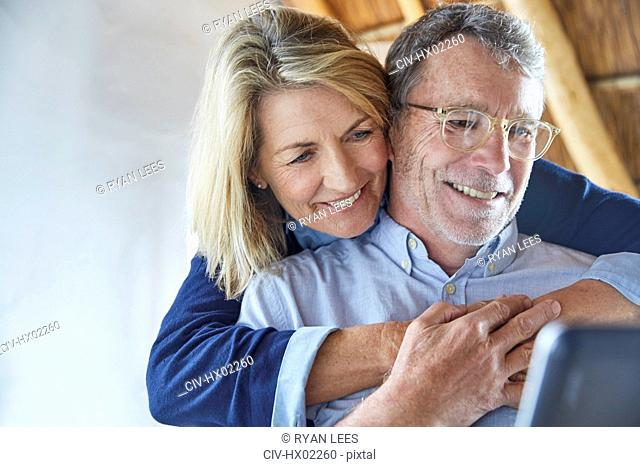 Affectionate couple hugging and using laptop