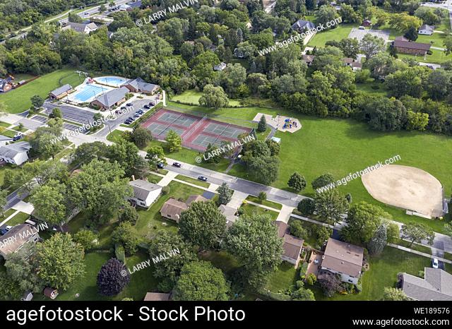Aerial view of a tree-lined neighborhood with a ballfield, tennis courts and swimming pool in a Chicago suburb during summer