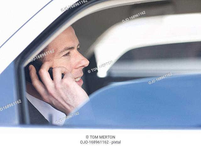 Politician talking on cell phone in backseat