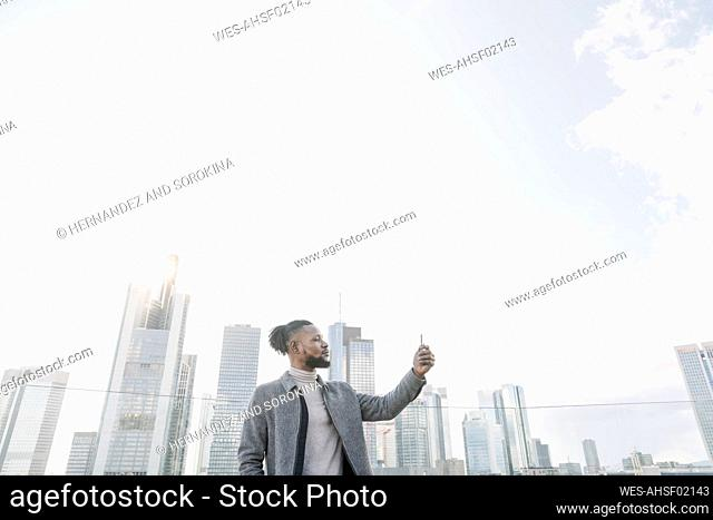 Stylish man on observation terrace taking a cell phone picture, Frankfurt, Germany