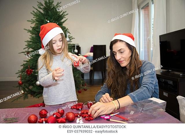 four years blonde cute girl with red Santa Claus hat and her woman mother preparing adornments for the Christmas tree, at home
