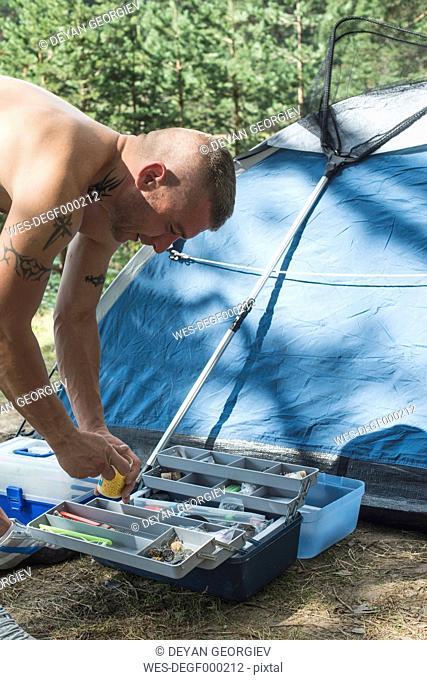 Bulgaria, man preparing hook for fishing