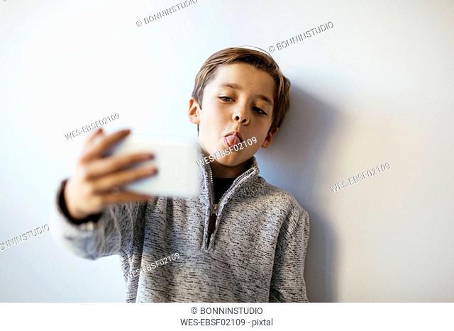 Boy taking selfie sticking out tongue