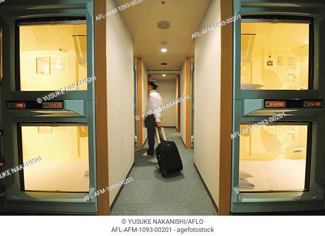 Businessman standing in capsule hotel