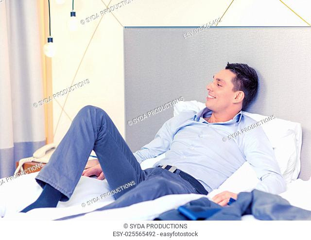 business, technology, internet and hotel concept - happy businesswoman lying in bed in hotel room